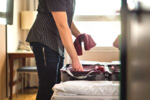 Man packing suitcase for vacation. Person putting clothes to baggagge in hotel room.